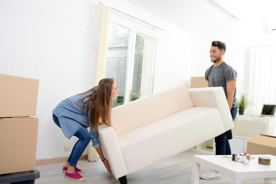 A photo of a young couple lifting their couch to be shipped.