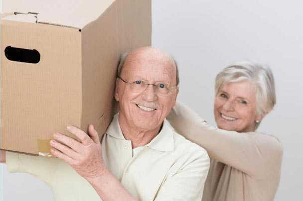 A elderly lady sitting on boxes that were shipped using our small moving services.