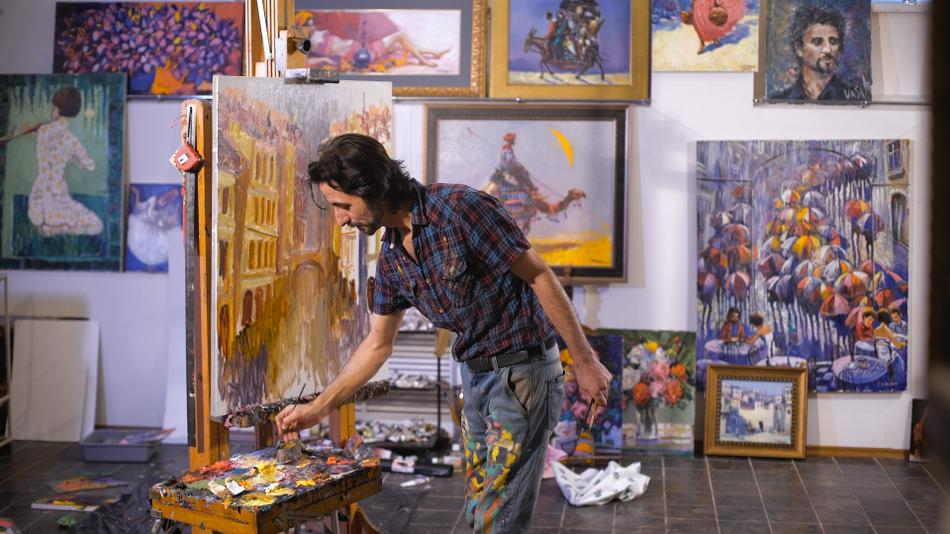 An artist painting a portrait in a room full of his paintings.