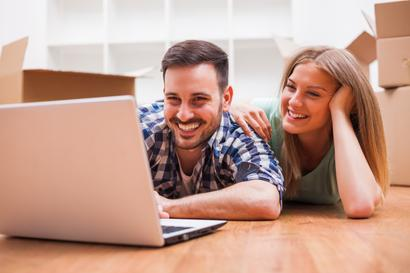 A couple on floor making their moving plan on a laptop.