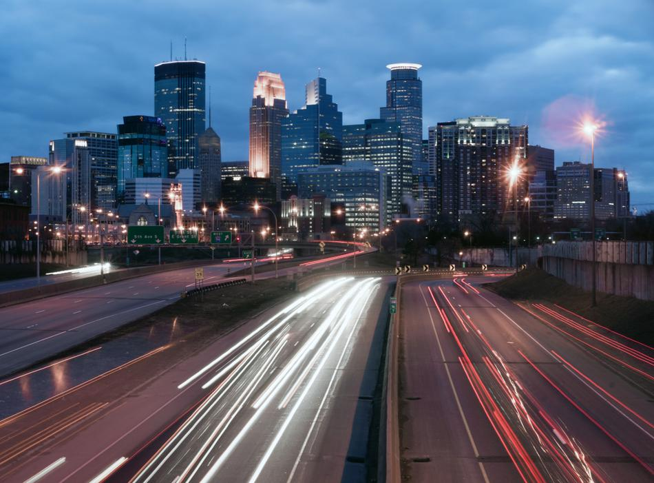 Minneapolis skyline with cars and trucks moving on the highway.