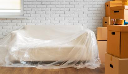 Picture of a elegant white couch wrapped in thick plastic ready to be packed and shipped state to state.