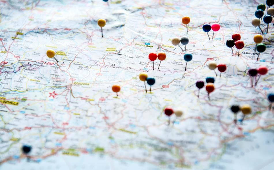 A map with push pins on possible travel destinations.