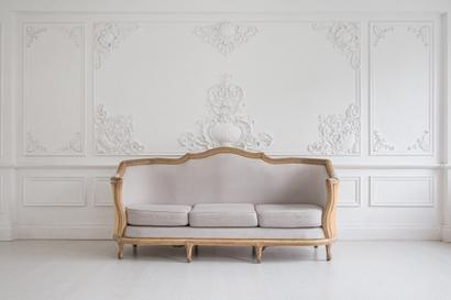 Beautiful white antique couch in an all white room needing to be packed and shipped for a customer.