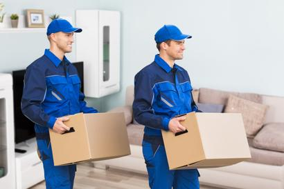 Two movers helping a customer with packing and moving boxes.